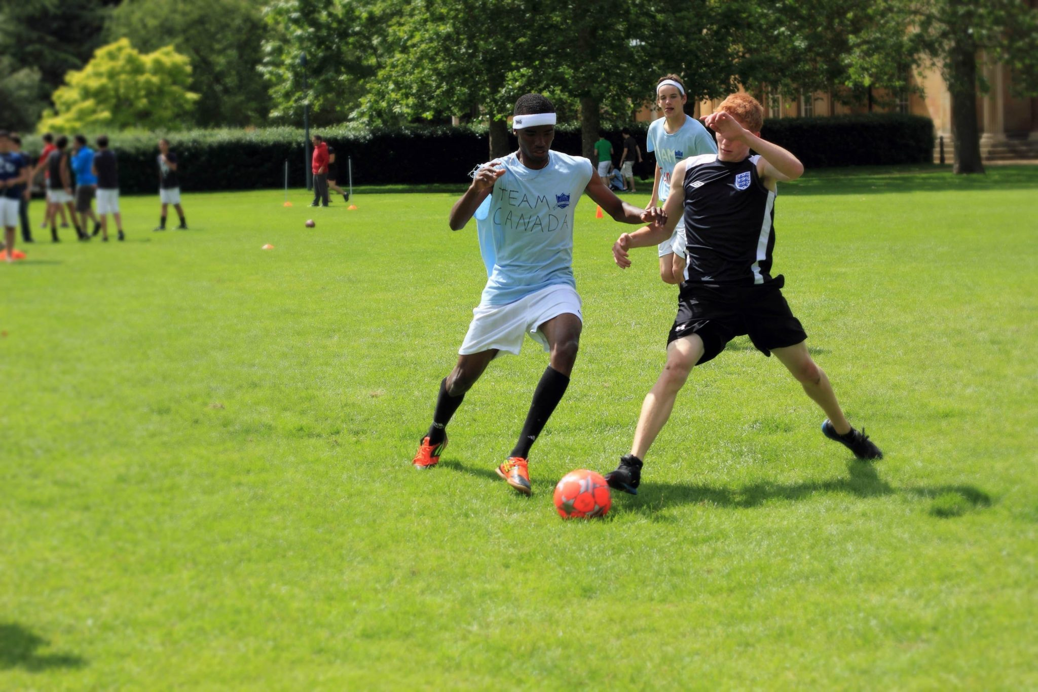 Two students play football on a green field. One student has red hair and is wearing their own sports kit, and the other student is wearing a customised 'Reach Cambridge' T-shirt. They are both running for the ball.
