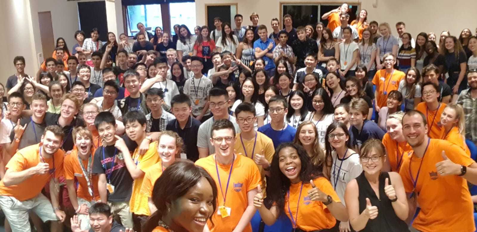 A wide-angle selfie of all of the students from a summer program. The Reach staff are at the front in orange T-shirts, looking happy and excited. The students are all standing behind, smiling.
