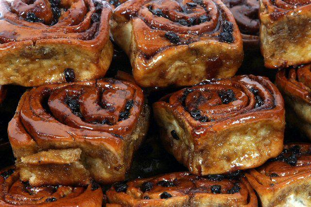Close-up of a pile of Fitzbillies Chelsea Buns, looking sticky and golden.