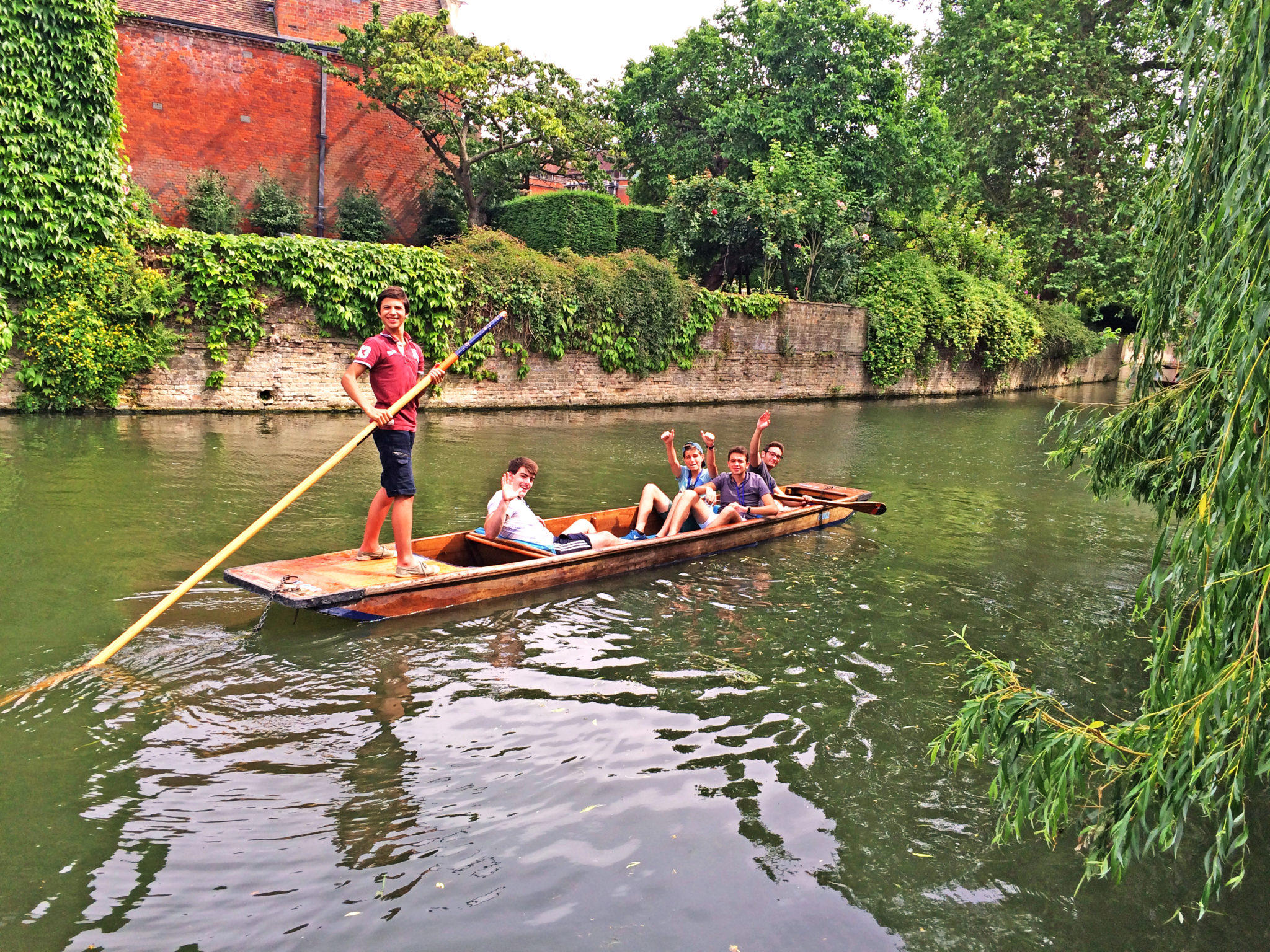 A group of students punting on the River Cam. One student stands at the back of the punt holding a pole. The others are sat in the boat, waving at the camera.