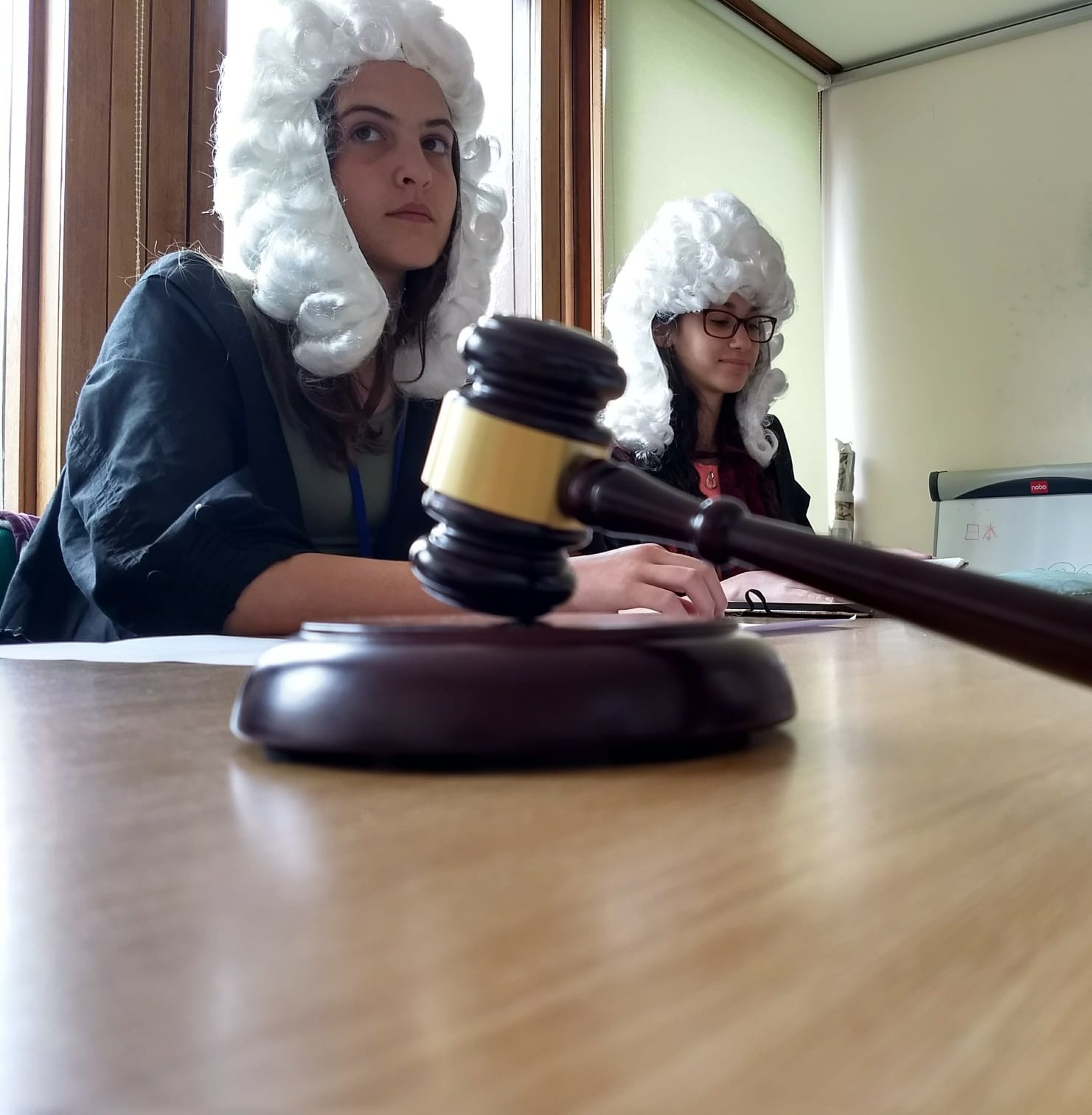 Two students sit at a classroom table, wearing fancy-dress judge wigs, in the background. In the foreground is a toy gavel resting on the table.