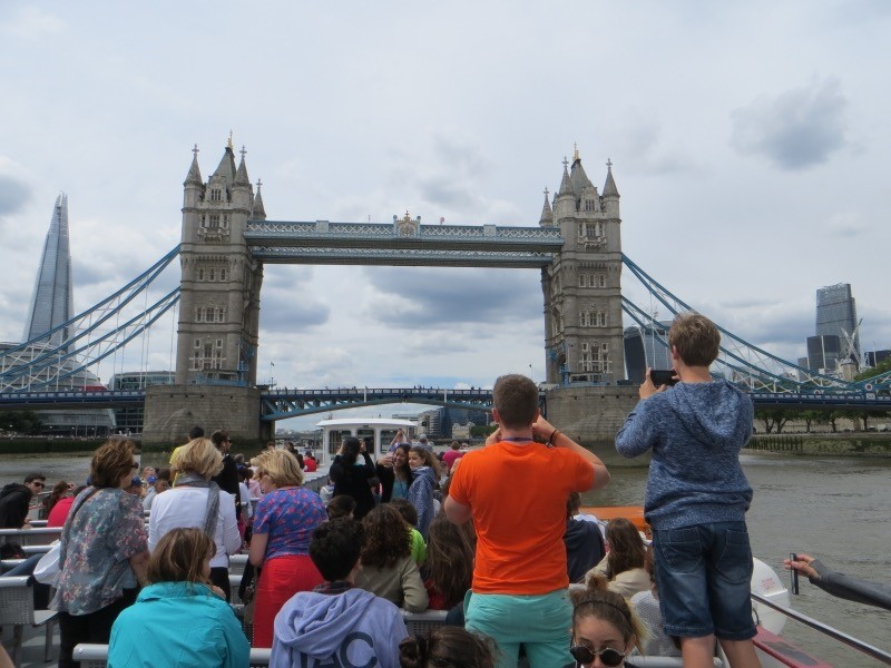In the background is London Bridge. In the foreground we can see the backs of a group of students, all taking pictures of the famous bridge.
