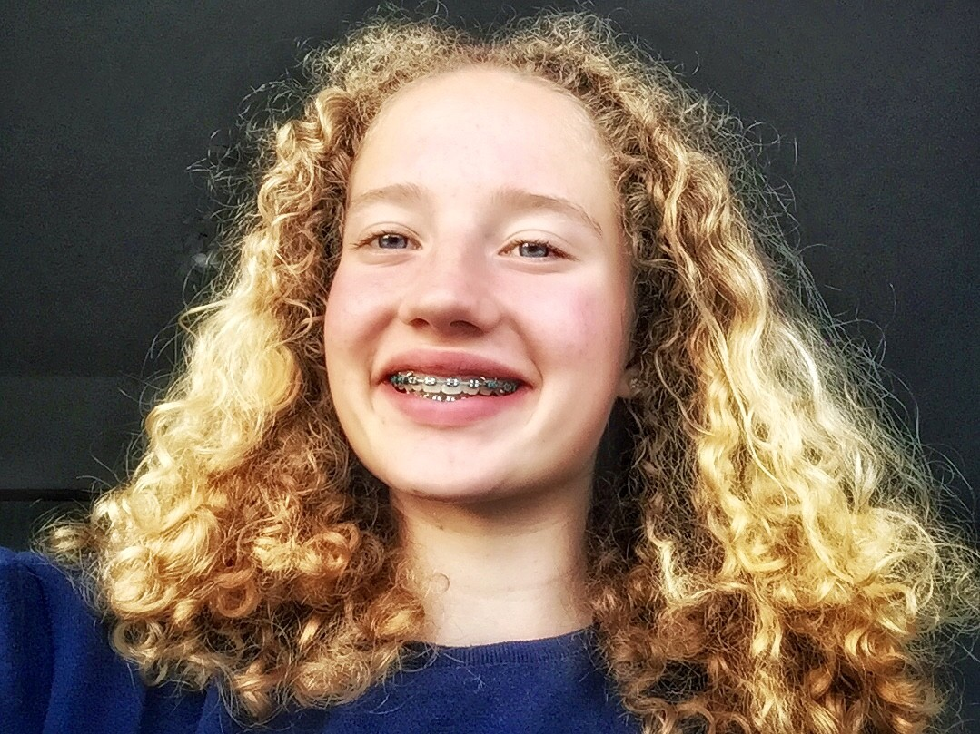 A selfie of Maggie. She has long curly long hair and blue eyes. Her wide smile shows her braces. She is wearing a blue jumper.
